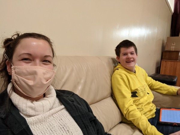 Alt text/ID: Guest blogger, Kylee Hooper is wearing a cream-colored turtleneck sweater, black jacket and a nude-colored face mask. She is socially distanced from but sharing a couch with a teenaged boy in a yellow hoodie with an AAC communication device on his lap. Both are smiling at the camera.